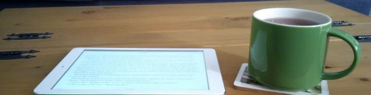 An ebook opened on an iPad with a cup of coffee next to it.